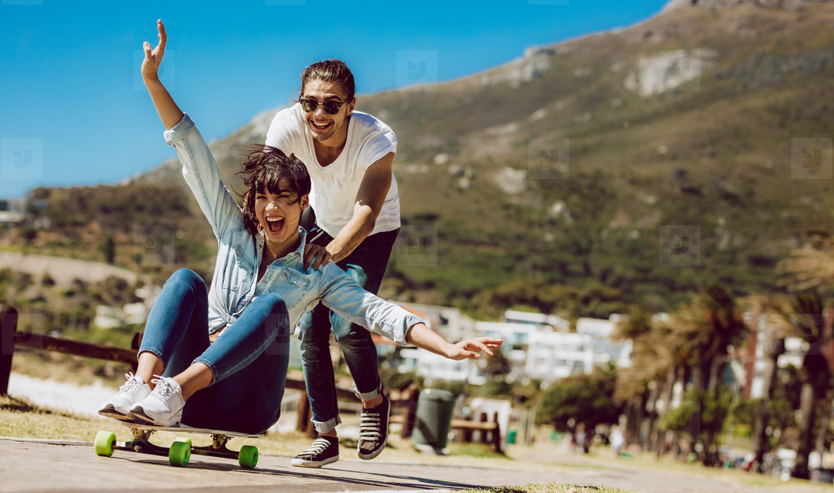Couple having fun with skateboard at the beach