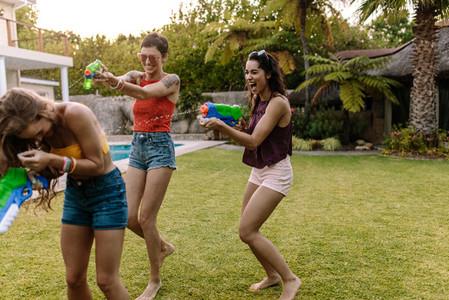 Friends having fun playing with water guns