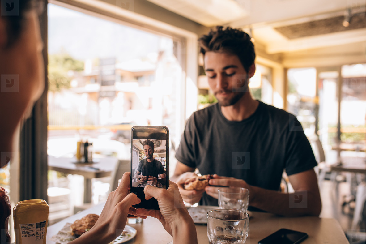 Woman capturing pictures of man eating burger