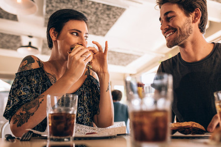 Couple at restaurant having burger