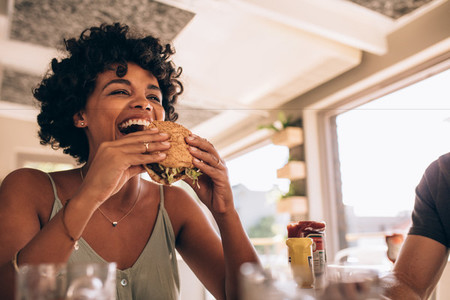 Woman enjoying eating burger at restaurant