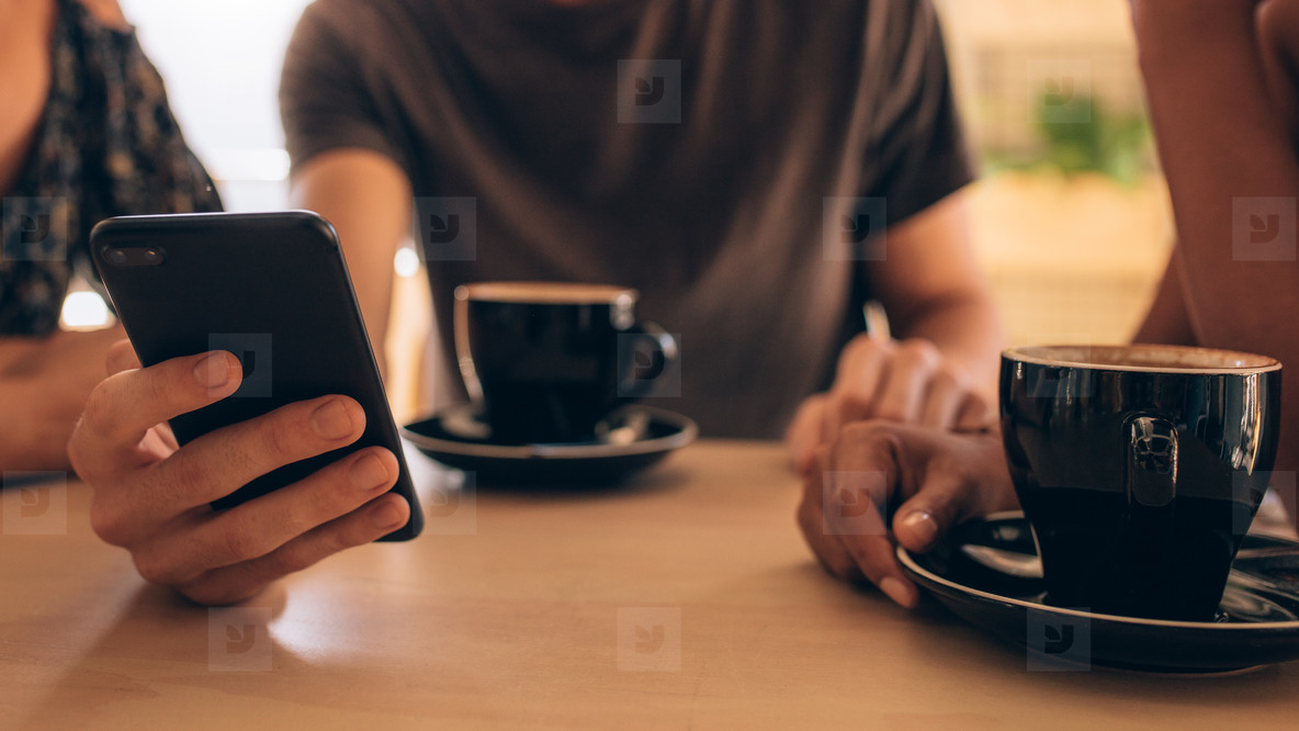 Young people at coffee shop with phone