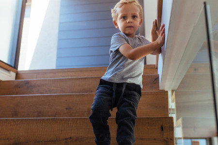 Little boy alone walking down stairs at home