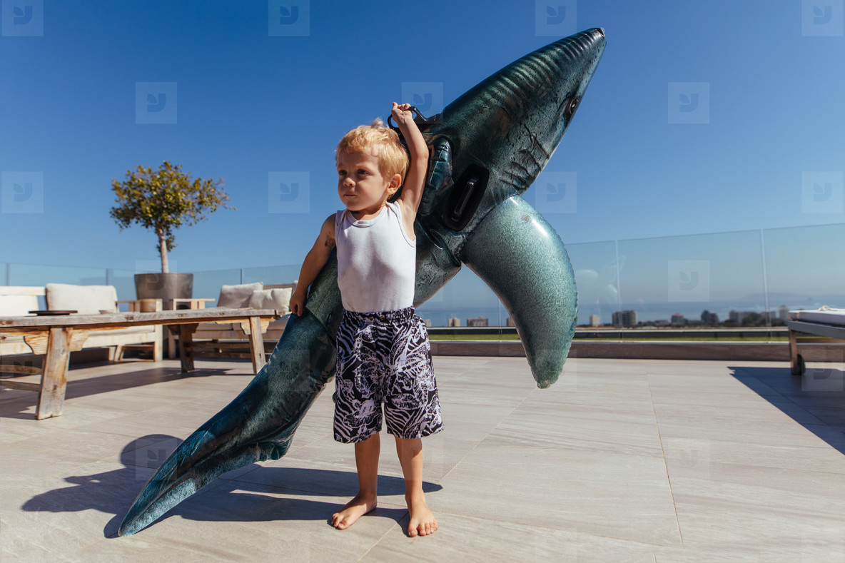 Little boy with a big pool toy
