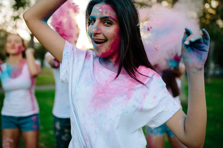 Woman celebrating festival of colors with friends