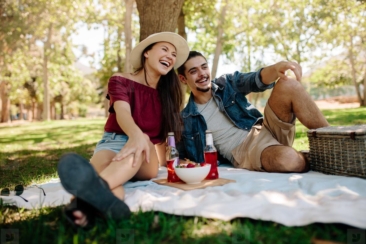 Cheerful couple having a picnic at city park