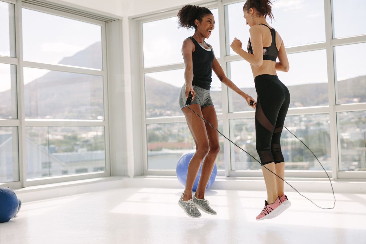 Women jumping together with skipping rope in gym