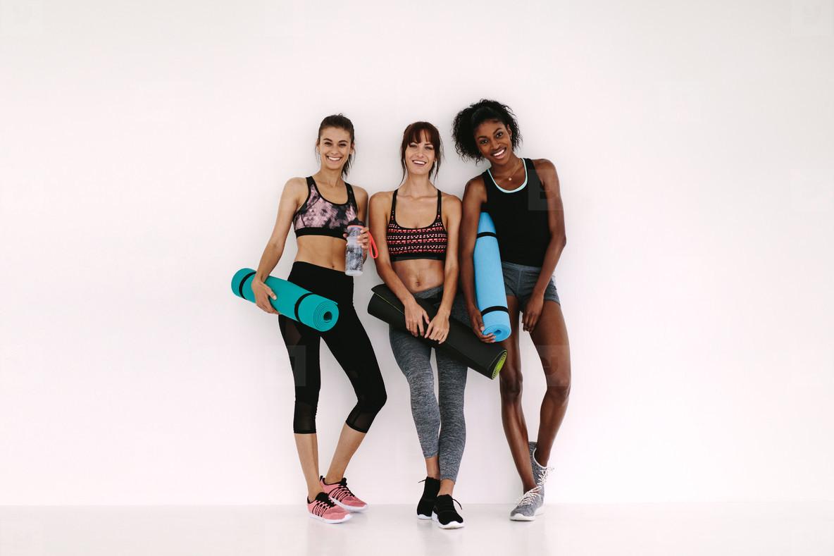 Sporty girls with fitness mat having a break