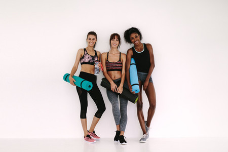 Sporty girls with fitness mat having a break