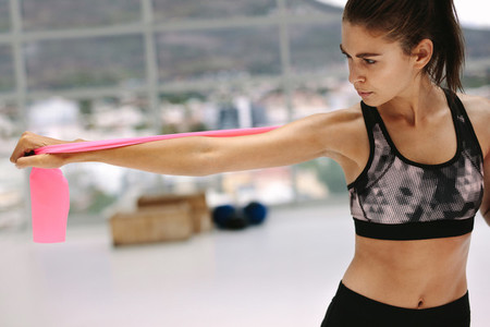 Health conscious woman exercising with resistance band
