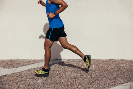 Athletic man jogging outdoors on sidewalk