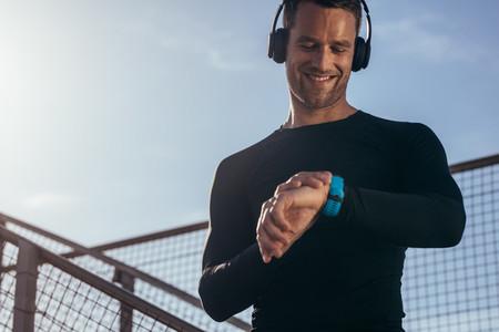 Athlete using smartwatch to monitor his progress