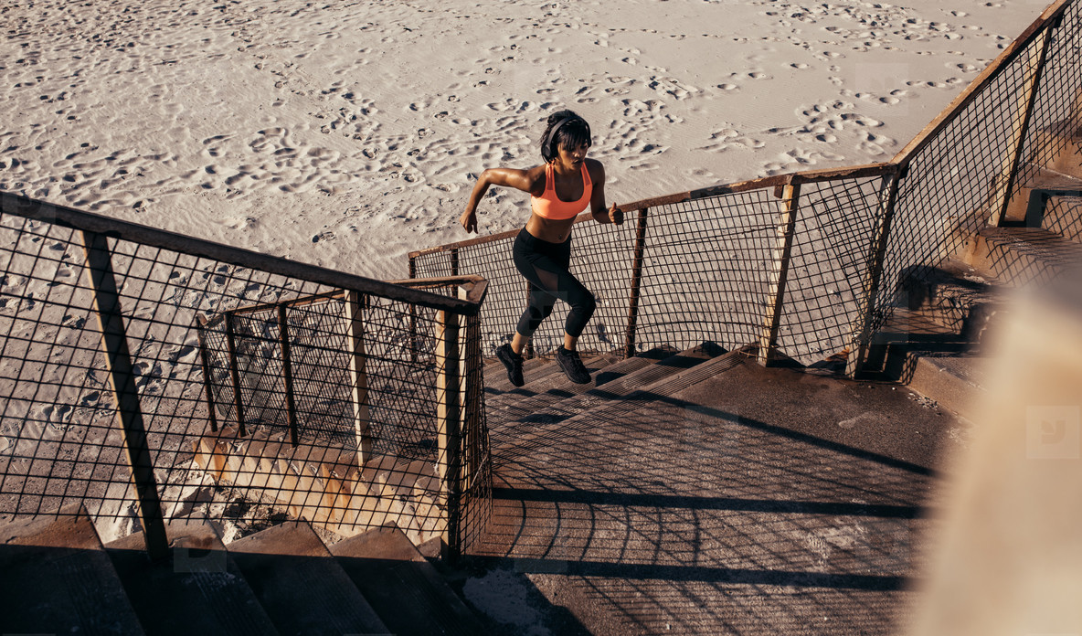 Athletic woman runs up the steps on the beach