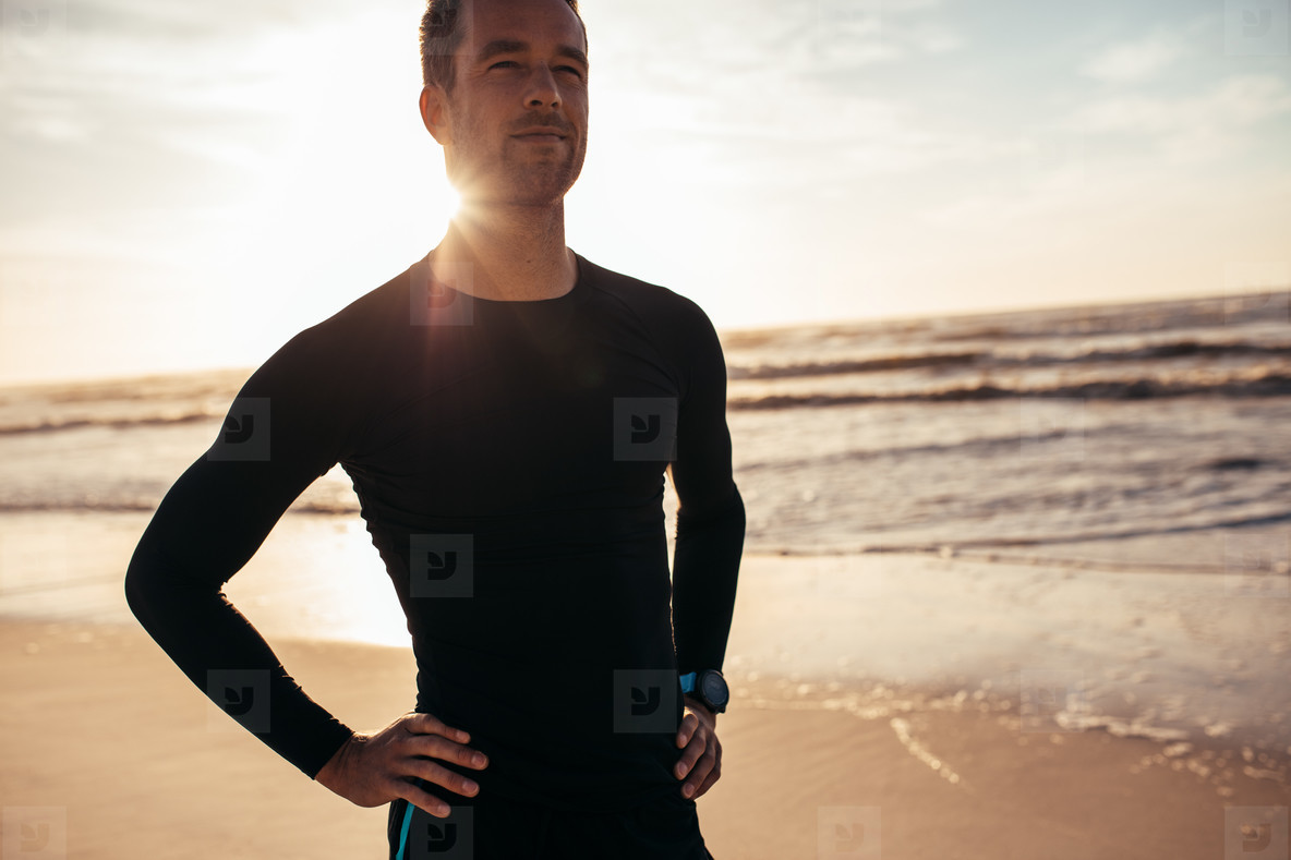 Confident male athlete standing on the beach