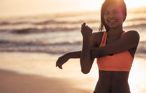 Smiling woman stretching arms at the beach