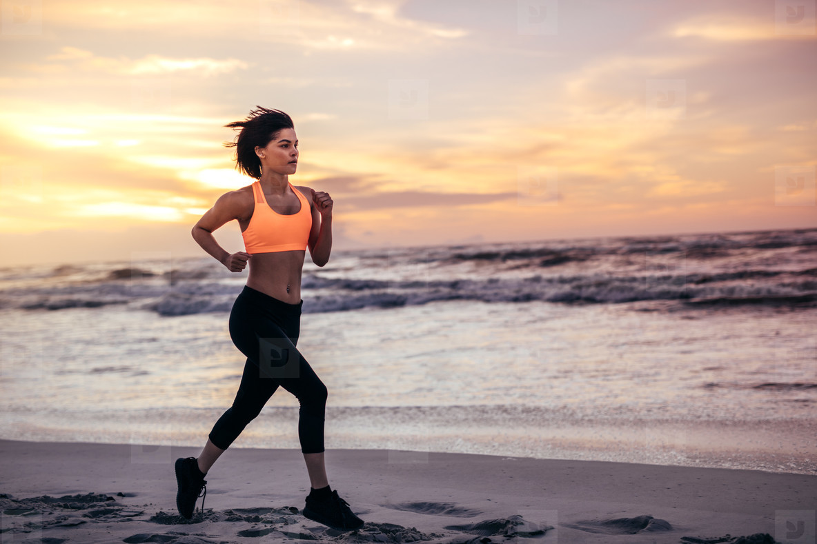 Woman athlete running along the beach in morning