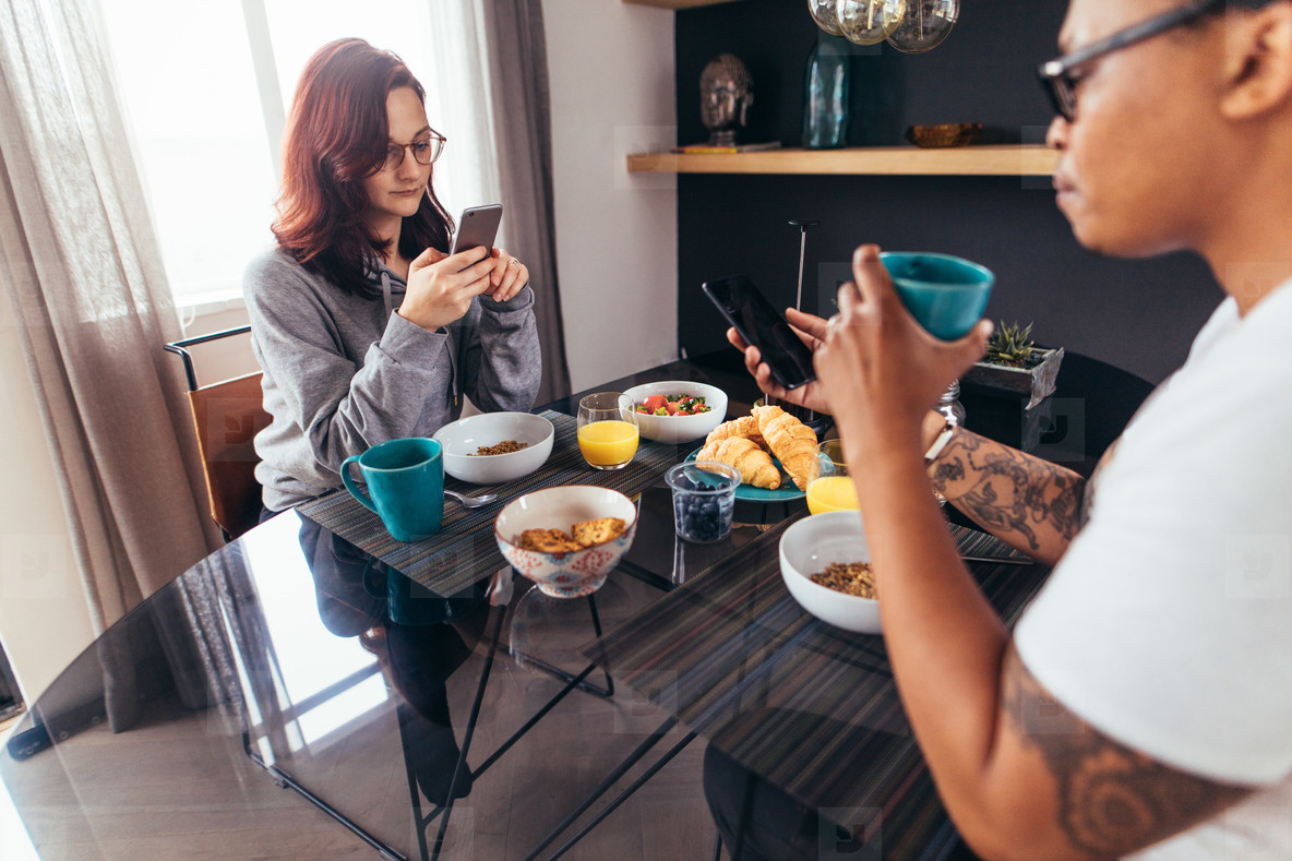 Couple at breakfast table using mobile phone