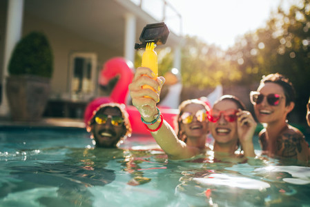 Woman with friends making selfie at pool party