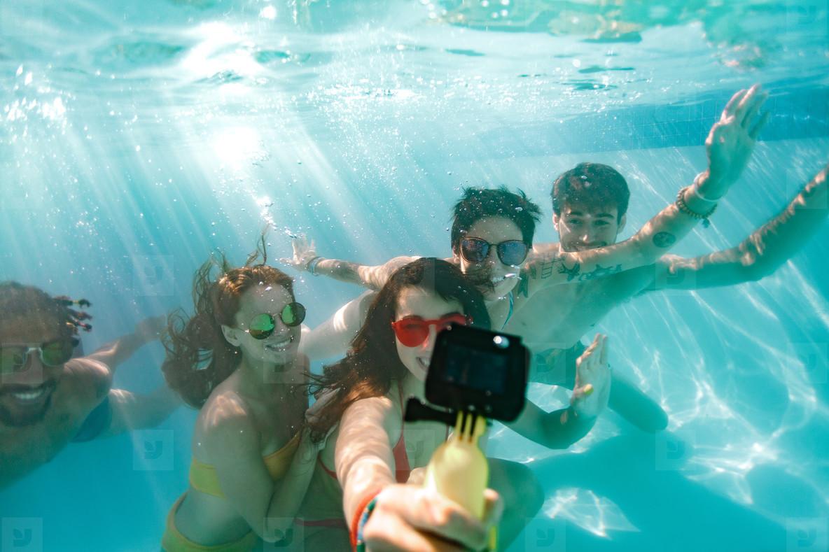 Friends taking selfie under the water in swimming pool