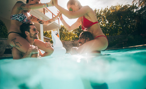 Couples playing and enjoying in a swimming pool