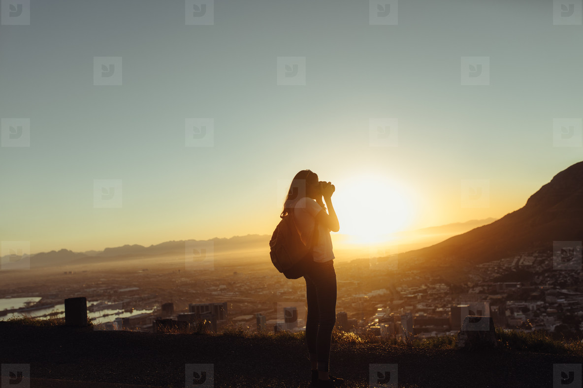 Female traveler taking pictures with camera