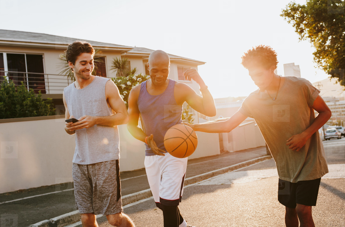 Basketball guys walking on street playing with the ball