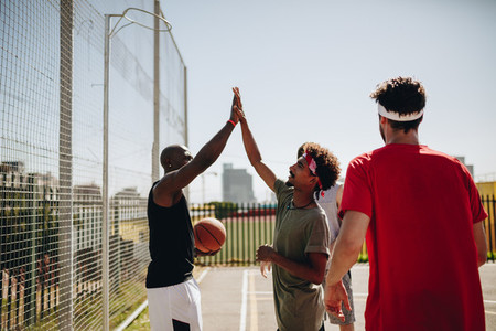 Men playing basketball in basketball court