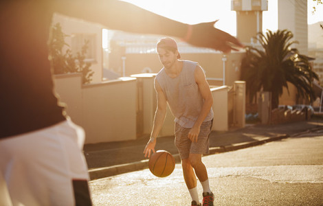 Men playing basketball on street