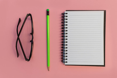 Education notebook pencil and eyeglasses on pink background