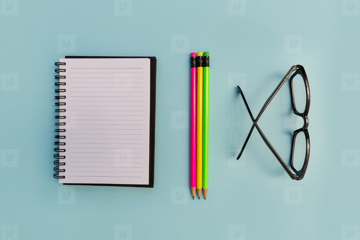 Education notebook pencil and eyeglasses on blue background