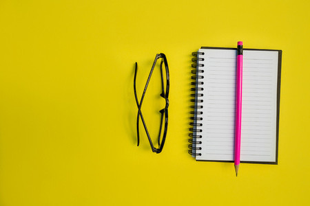 Education notebook pencil and eyeglasses on yellow background