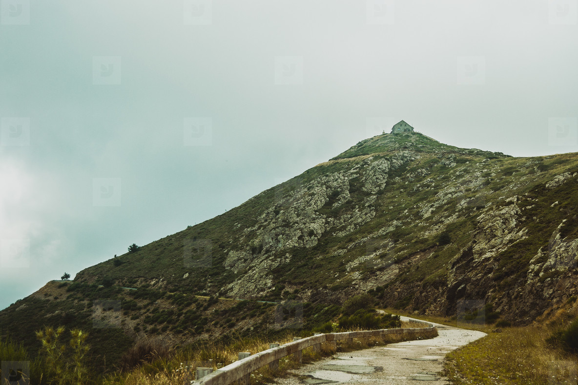 stone house on top of a mountain peak on a cloudy day