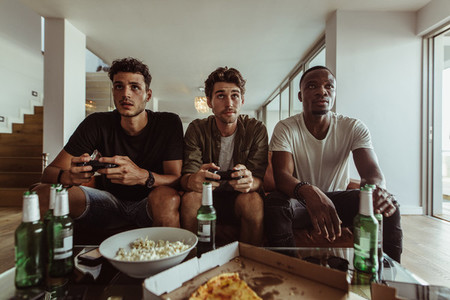 Friends playing video game sitting at home