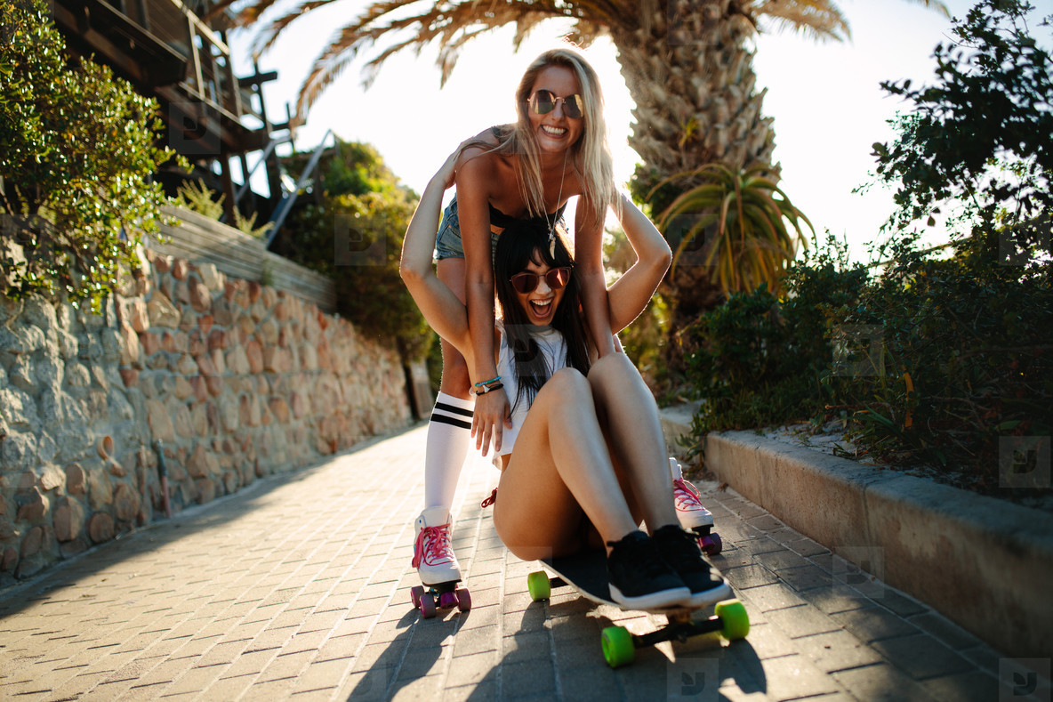 Female friends having fun with a skateboard