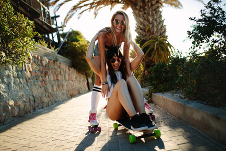 Female friends having fun with a skateboard