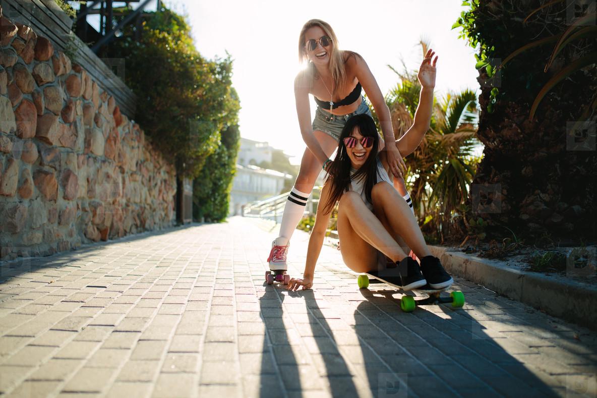 Female friends having fun with skateboard