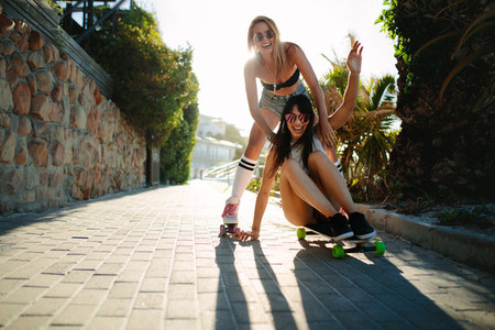 Female friends having fun with skateboard