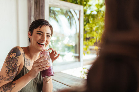Woman drinking a smoothie at a restaurant