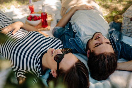 Cheerful couple on picnic at park