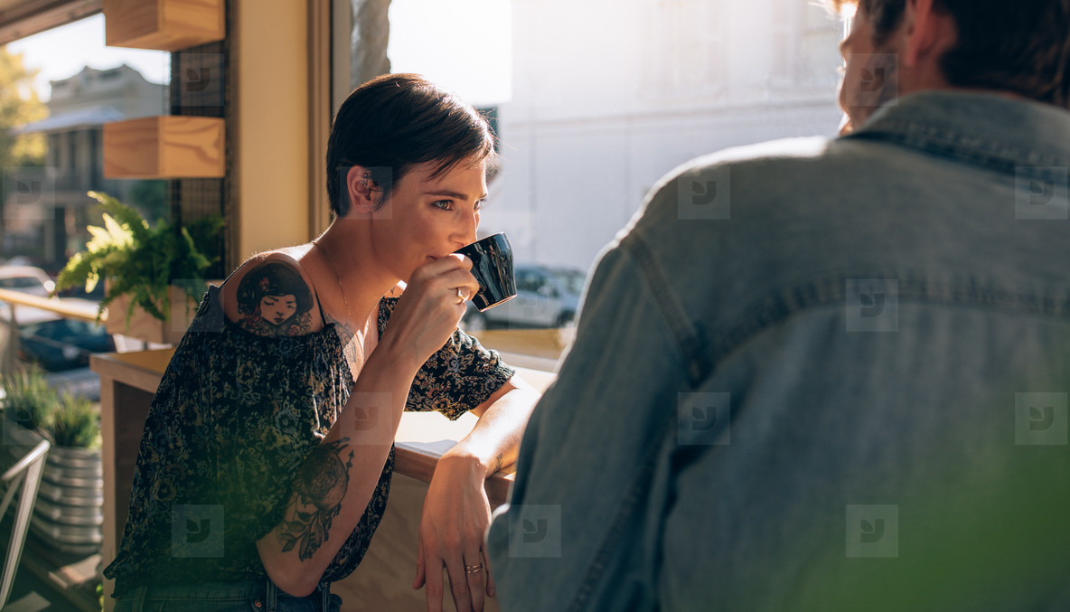 Woman drinking coffee her friend
