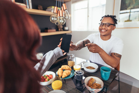 Couple at breakfast table with phone