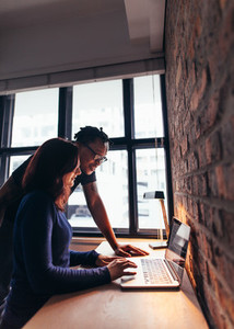 Woman working on laptop with man standing by