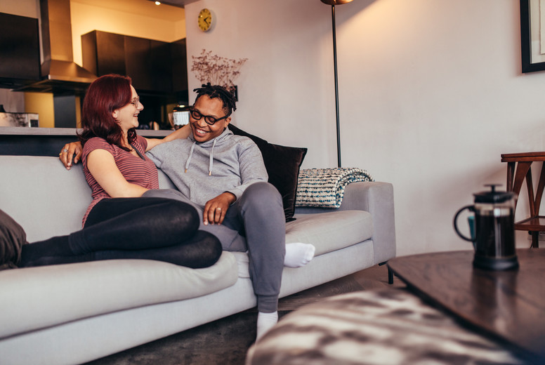 Cheerful interracial couple relaxing on couch
