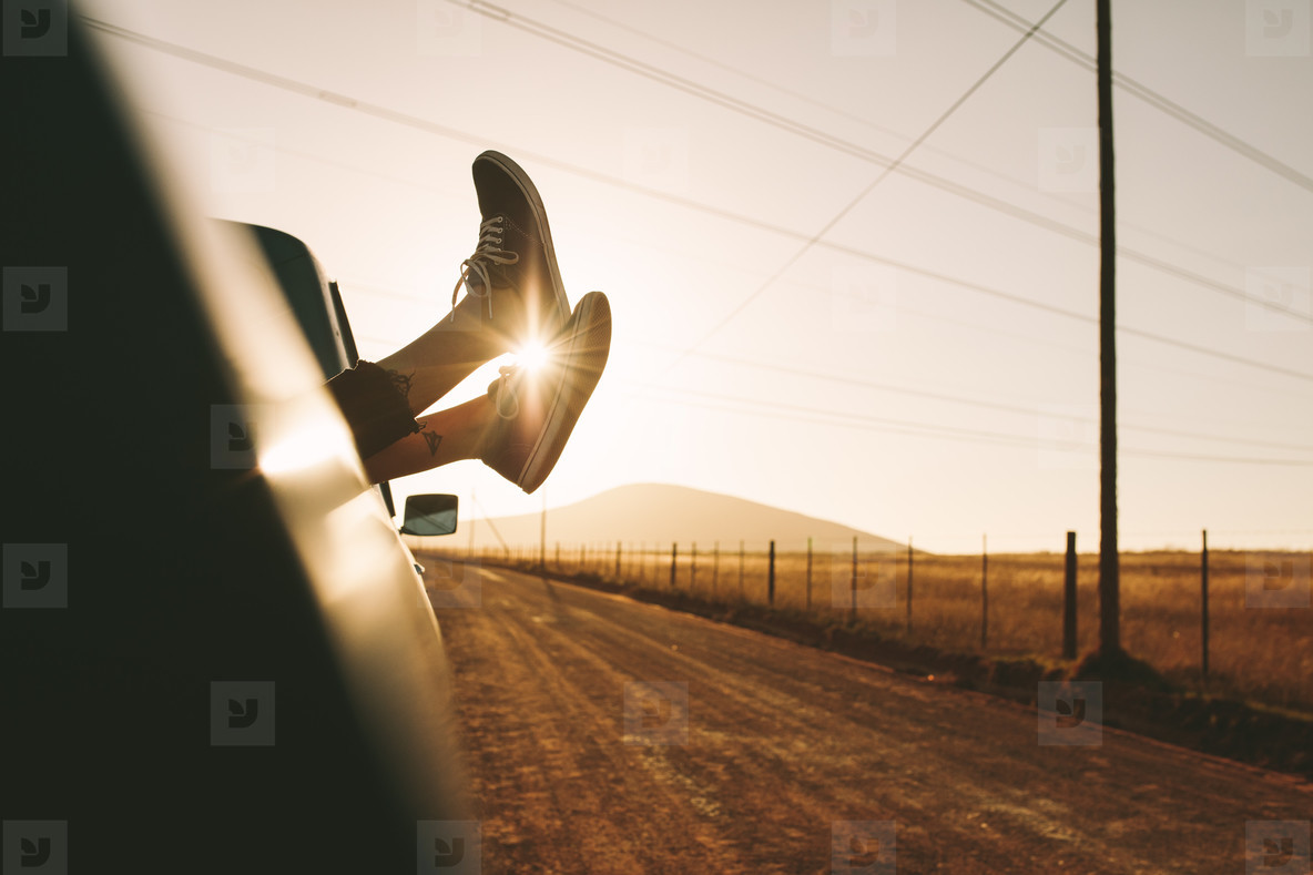 Legs hanging out of a car on highway