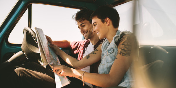 Young travellers on a road trip looking at map
