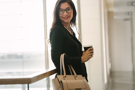 Business woman standing by a railing with coffee