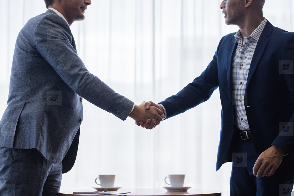 Business men shaking hands with each other after a deal