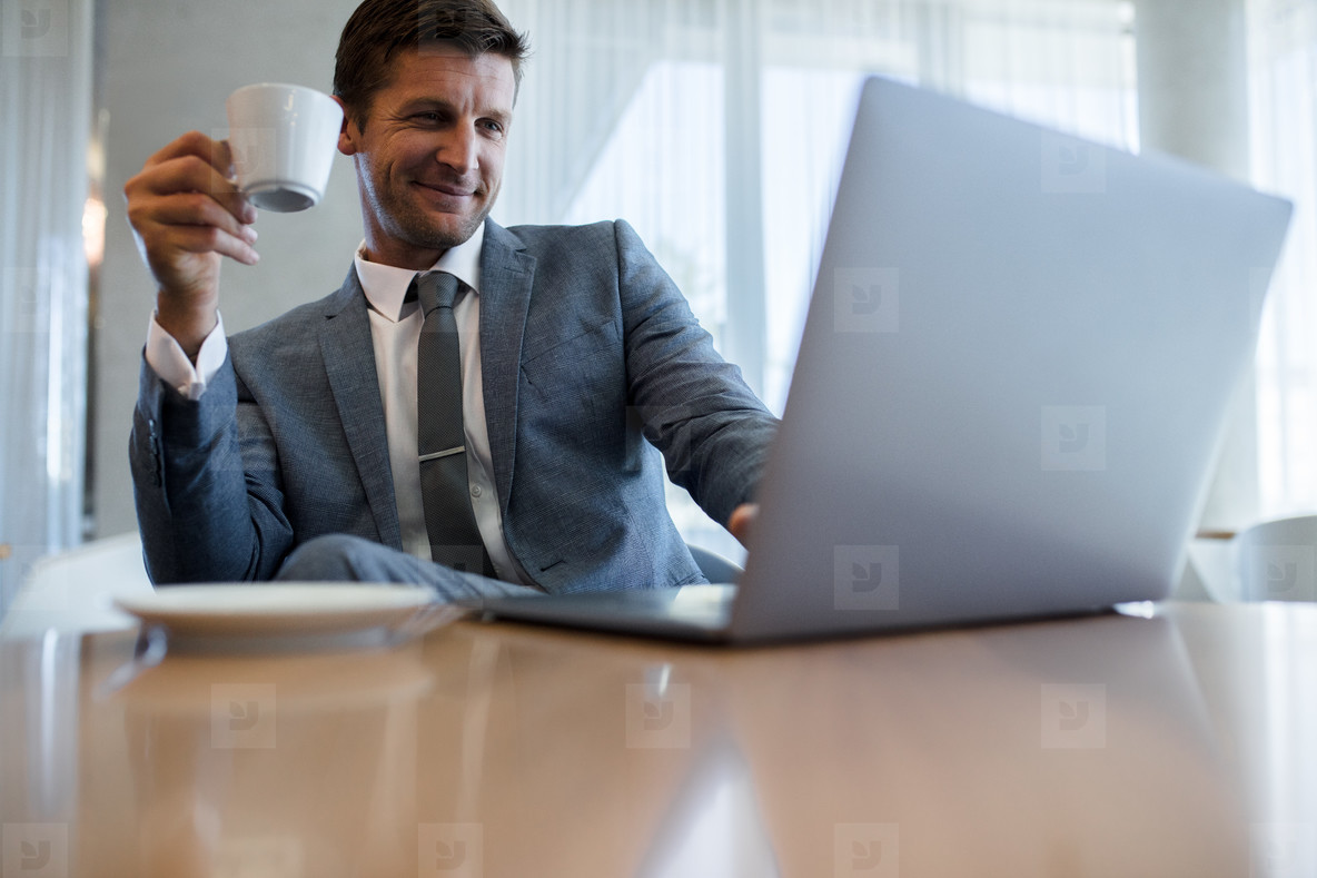 Businessman using laptop and having coffee at office