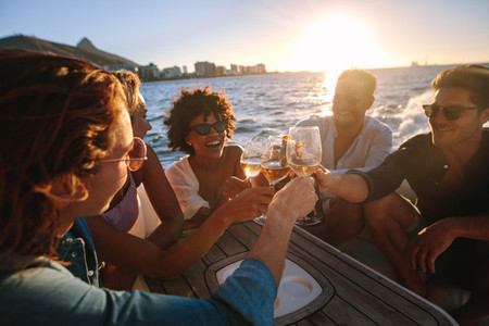 Cheerful friends drinking together on yacht