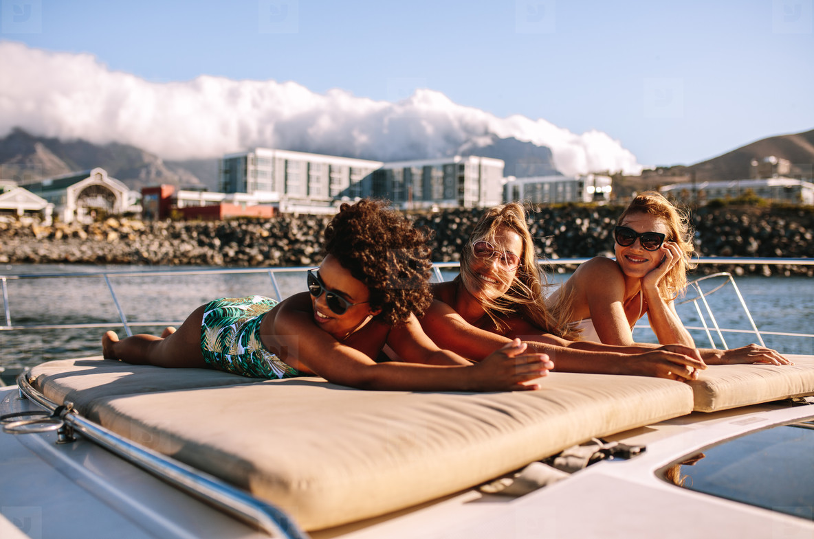 Female friends sunbathing on the bow of a luxury yacht